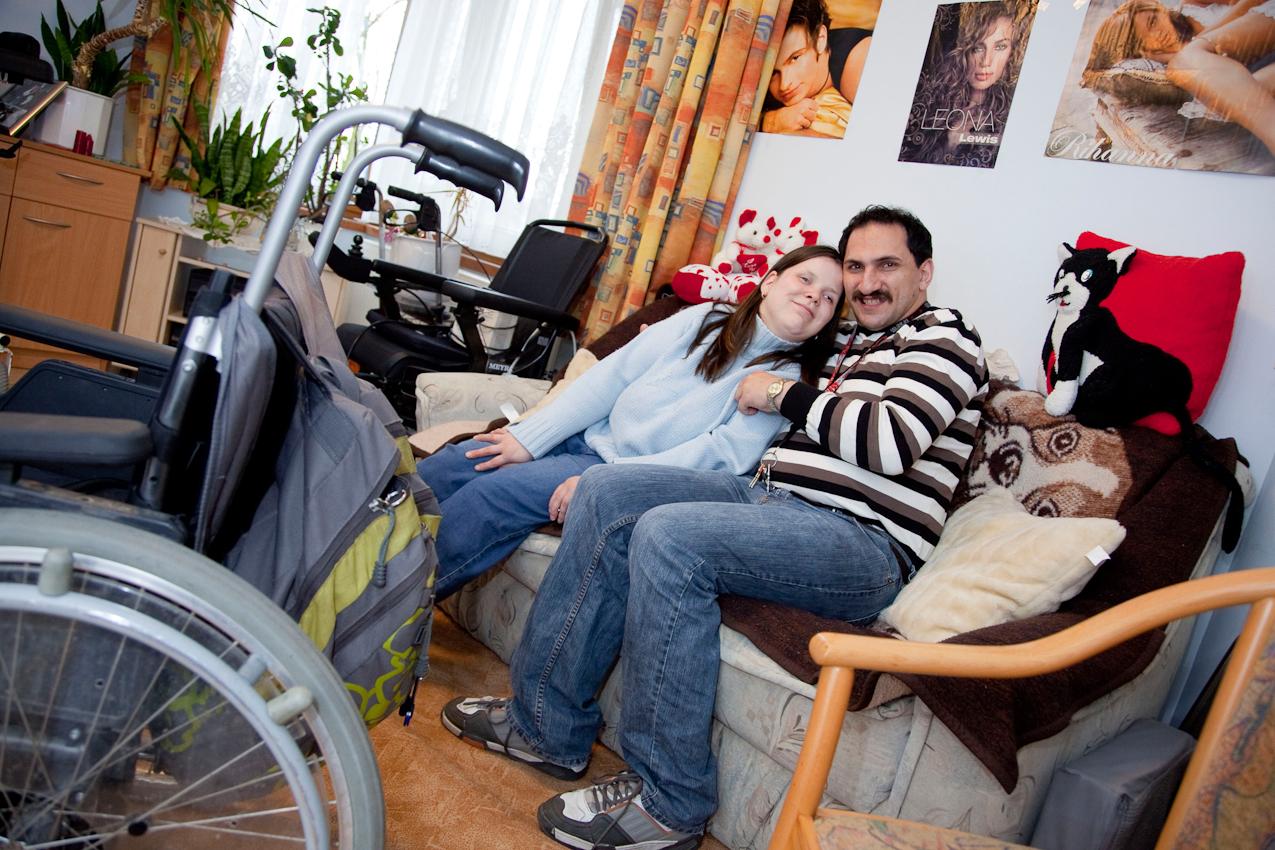 """Nicole Frenzel & Michael Knoll leben in der Wohnstätte der ,,Hoffnungstaler Anstalten Lobetal"""" im Johann-Hinrich Wichern Haus in 16321 Rudnitz. Die Bewohner werden hier entsprechend ihres Behinderungsgrades durch fachkompetente Mitarbeiter betreut, unterstützt und beim Tagesablauf begleitet.  Sie lernen unter Anleitung des Pflege- und sozialpädagogischen Personals mit ihren Handicaps umzugehen. Soweit es ihre Behinderungen erlauben, lernen sie alltägliche Dinge des Lebens selbstständig zu verrichten und erleben dadurch Freude, Achtung und Anerkennung. Nicole und Michael helfen sich sehr liebevoll gegenseitig bei den alltäglichen Dingen. Hier befinden sie sich glücklich miteinander im persönlichen Wohnraum.  16321 Rudnitz am 07. Mai 2010"""
