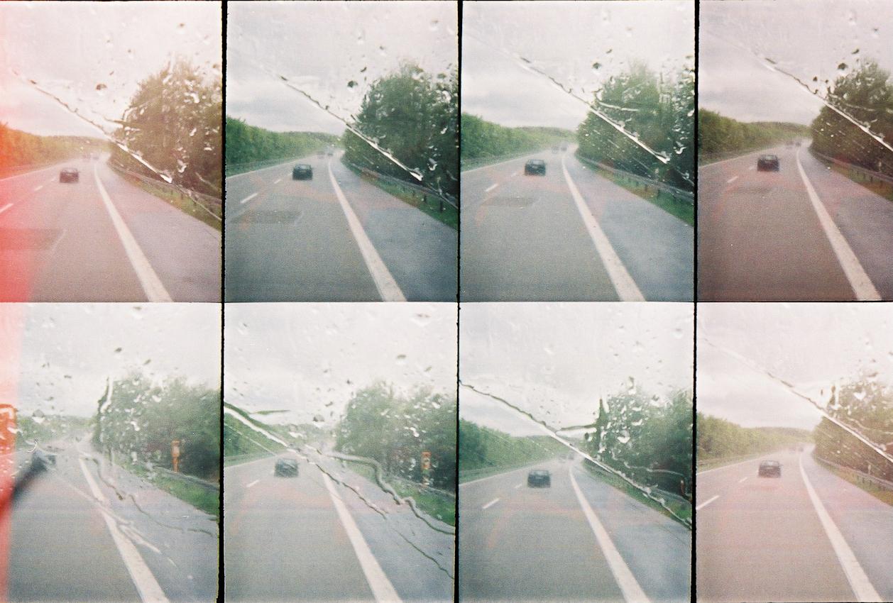 Ein Roadmovie in 8 Bildern - zweieinhalb Sekunden Deutschland: Die Meteorologen behalten leider recht: Der 7. Mai 2010 ist kalt, nass und truebe ... im Hochsauerland liegt sogar wieder Schnee. Unser Oldtimer-Bus erreicht maximal 85 km/h, das Radio ist defekt - die Fahrt auf der Autobahn loest sich auf in einem einschlaefernden Rythmus aus quietscheden Scheibenwischern, ueberholenden PKWs und monotoner Landschaft.  Analoge Charakteristik ist beabsichtigt. Lomografie mit Oktomat (8-fach Bild).