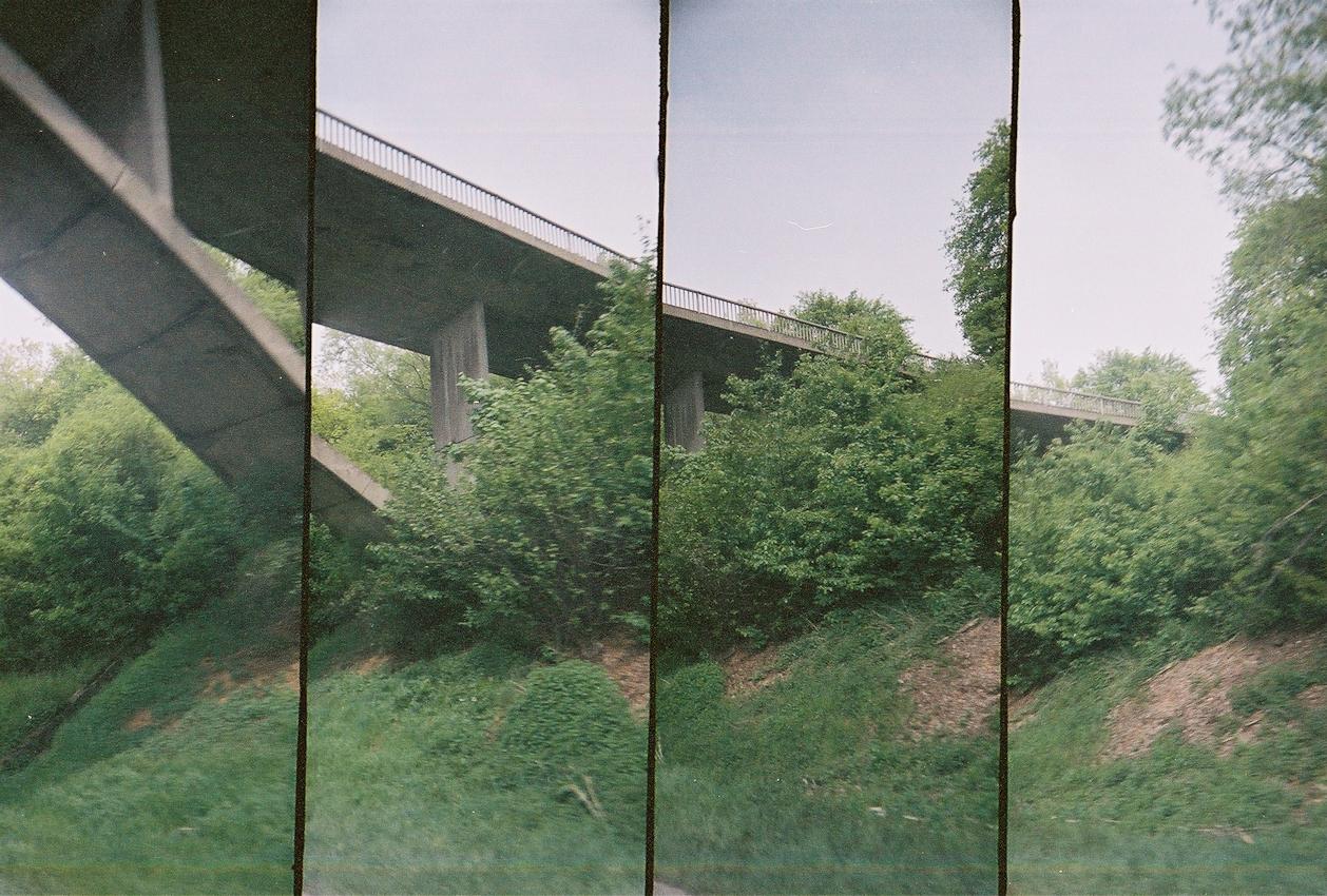 Ein Roadmovie in 4 Bildern: Die Sauerlandlinie teilt Waelder und Felder auf ihrem Weg zwischen Dortmund und Aschaffenburg. Neben den >>normalen<< Bruecken fuer den fliessenden Verkehr, verbinden einige Bruecken auch die Feldwege beider Seiten der Autobahn: Zwischen der Anschlussstelle Giessen-Luetzellinden und der Talbruecke Muenchholzhausen wird die Sauerlandlinie (A45) seit Beginn der 1970er Jahre von einer formschoenen Stahlbetonbogenbruecke ueberspannt. Analoge Charakteristik ist beabsichtigt. Lomografie mit Super-Sampler (4-fach Bild).