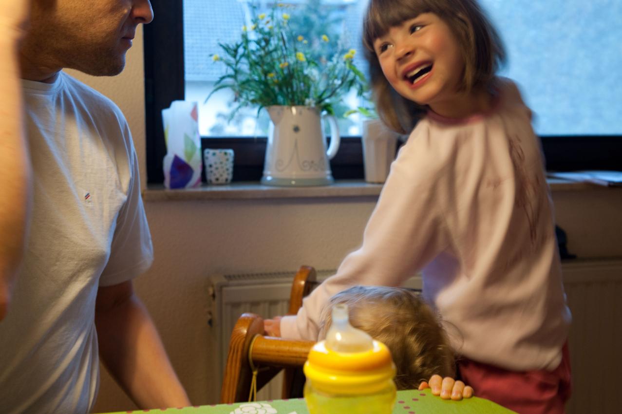 """07.19 Uhr, Küche: Direkt nach dem Aufstehen flitzt Nia in die Küche und begrüßt gut gelaunt ihren Vater, der sie jeden Morgen nach dem gemeinsamen Frühstück in den Kindergarten bringt, wo sie bis mittags bleibt und dann von ihre Mutter abgeholt wird.  Das Foto wurde am 07.05.2010 für das Projekt """"Ein Tag Deutschland"""" aufgenommen im Rahmen einer Fotoserie über das Alltagsleben einer Kleinfamilie im Dorf Maintal-Wachenbuchen, 15 Km östlich von Frankfurt am Main. Bei der Serie geht es darum den normalen Alltag eine Kleinfamilie zu zeigen, bei der nach klassischem Rollenmodell vorwiegend die Mutter für die Erziehung der Kinder zuständig ist. Die Mutter arbeitet freiberuflich als Fotografin, der Vater geht einem klassischen Bürojob nach und arbeitet jeden Tag 20 km entfernt. Miteinander, Nebeneinander und Gegeneinander sind das Thema der Serie mit Fokus auf der Beziehung der Geschwister untereinander, die den Familienalltag maßgeblich mitbestimmen. Die Serie über den Familienalltag ist als Langzeitprojekt angelegt. Die Fotos entstanden alle in der Wohnung der Familie, die Dreh- und Angelpunkt des Familienlebens ist. Zur Familie gehören der Vater Thomas Schäfer, die Mutter Meike Fischer (die auch fotografiert hat), die 5-jahrige Tochter Nia und der 14 Monate alte Sohn Levin."""