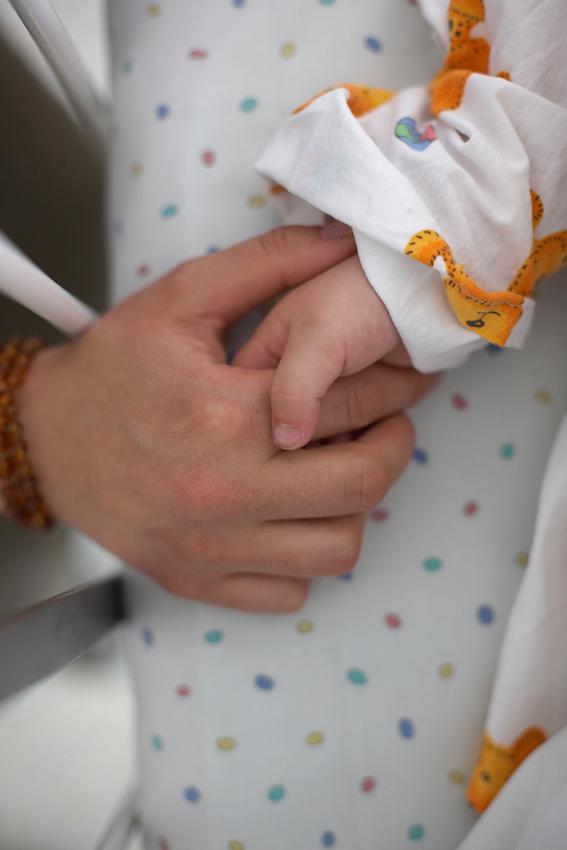 Mama Juliane hält kurz nach der OP Lucy's Hand