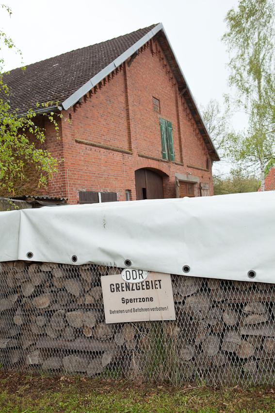 Reste der ehemaligen Grenzbefestigung der innerdeutschen Grenze hat eine Hausbesitzer am Brennholzstapel seines Hauses in einem Dorf an der ehemaligen Grenze befestigt.
