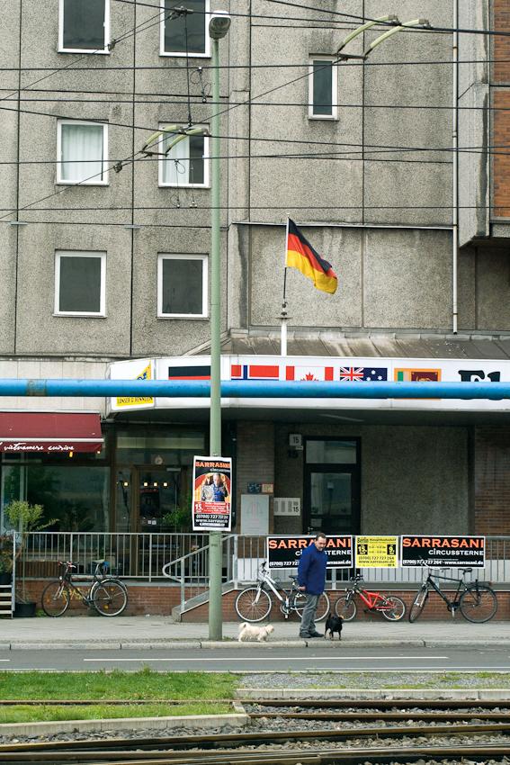 07.05.2010, 13:23 Uhr. Deutschland, Berlin. Alexanderplatz. Deutschlandfahne vor der grauen Fassade eines Plattenbaus an der Karl-Liebknecht-Straße. Davor steht ein Mann mit seinen beiden Hunden.
