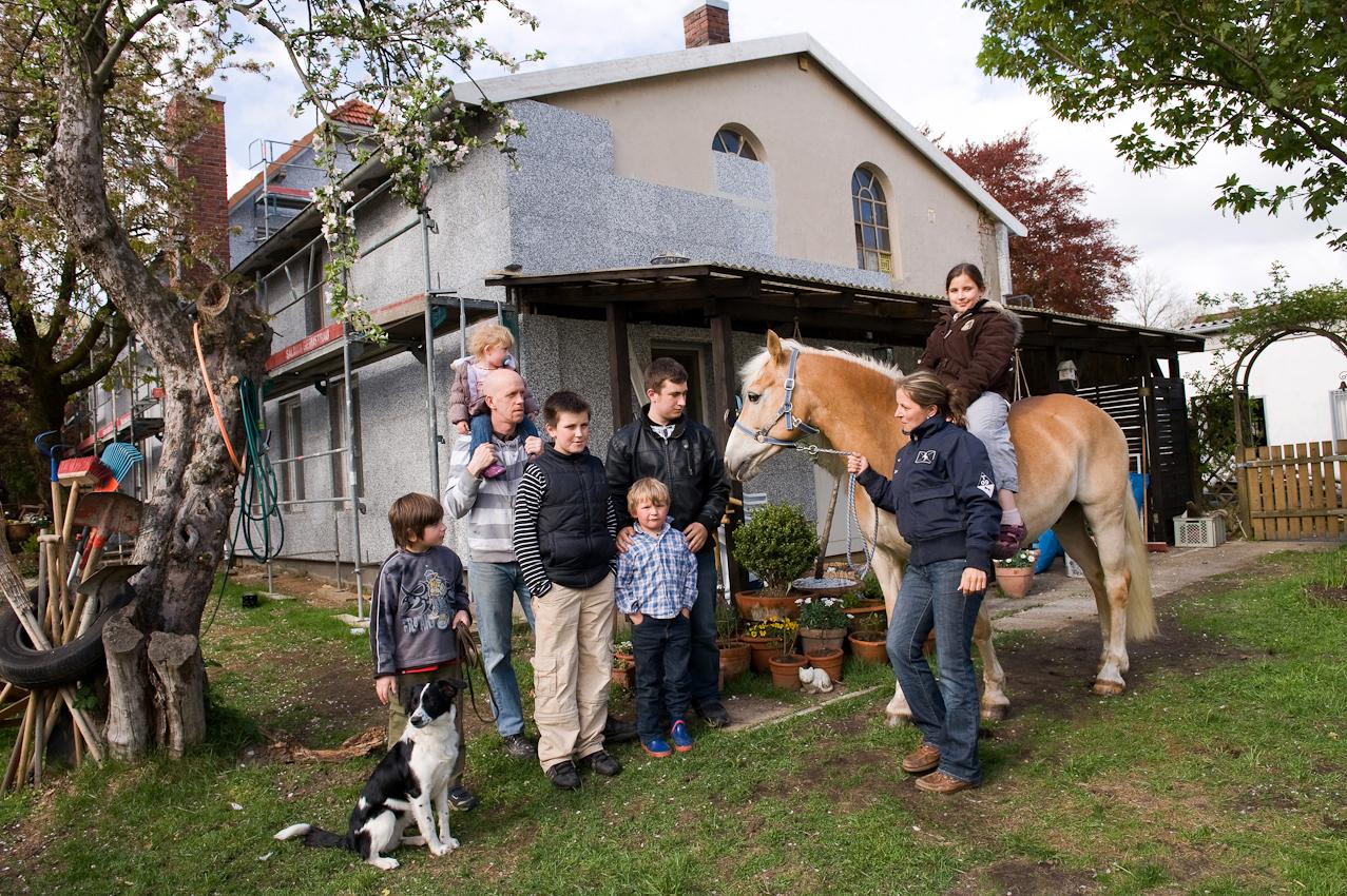 """Familie Töpfer vor ihrem Haus in Pinneberg bei Hamburg. Steffi ist 32 Jahre und Mutter von sechs Kindern im Alter zwischen 2 und 14 Jahren. Zur Familie gehören auch noch Hasen, zwei Katzen, Hund Lilo und Pferd Askari. ,,Die sechs Kinder waren alle geplant,"""" sagt Steffi. ,,Der Zusammenhalt in der Familie und Austausch untereinander ist schon."""" Sie ist als Einzelkind aufgewachsen und hat sich schon immer eine große Familie gewünscht. Alle passen aufeinander auf, die Kinder werden in der Gemeinschaft schnell selbständig und übernehmen viele Aufgaben. Viele Großfamilien werden in Deutschland abgestempelt, dass sie von Hartz IV leben wurden und verwahrlost sind. Familie Töpfer aus Pinneberg bei Hamburg kennt diese Vorurteile gut. Der Vater Frank, 38 Jahre, arbeitet bei Harry Brot und verdient den Lebensunterhalt alleine. Während er Wechselschicht hat, kümmert Steffi sich um die Kinder und alle anfallenden Arbeiten im Haus und Pferdestall."""