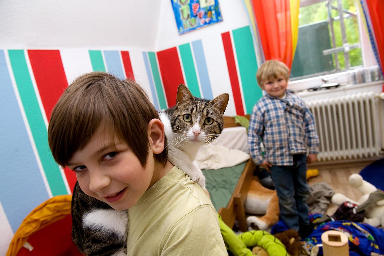 Yannis (8 Jahre) mit Katze Tiffy in seinem Zimmer, im Hintergrund ist Paul (5 Jahre). Jedes Kind hat sein eigenes Zimmer im Haus, je drei Geschwister teilen sich gemeinsam ein Badezimmer.