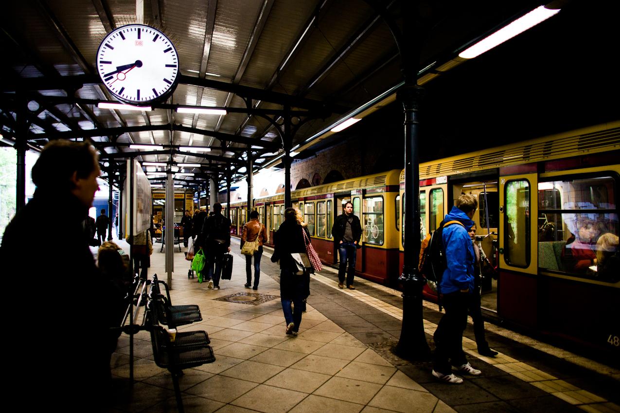 Fahrgaeste warten auf dem Bahnsteig auf die einfahrende S-Bahn an dem S-Bahnhof Schoenhauser Allee.