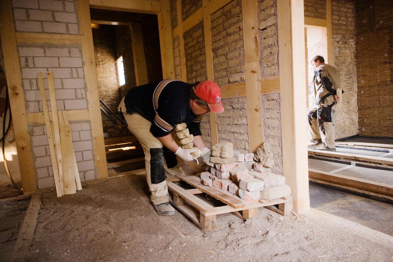 Sanierung eines Fachwerkhauses von 1582 in Arnstadt, Thüringen. Links die alte Bodenschüttung, rechts die sanierte Decke mit mit Fehlboden und Rieselschutzflies. Bevor die Schüttung umgeschaufelt wird, wird aufgeräumt.