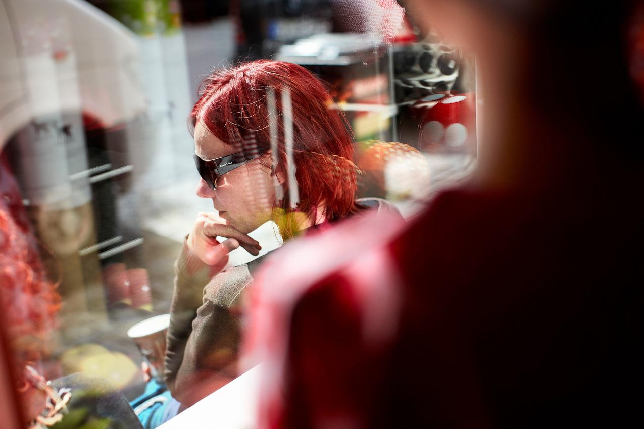 """15.43 Uhr, Ravensburg: Sonnenbad - Die gemütliche Athmosphäre des Kuschelwerks lädt zum Entspannen und Verweilen ein. Vor dem nächsten Regen tanken Petra und Doro (rechts) ein bisschen Sonne.  Nach der Geburt ihres Sohnes Lasse und der vergeblichen Suche nach dem etwas anderen Plüschtier fasst sich die Schneiderin Anke Mayer ein Herz und erfüllt sich einen Traum: Sie eröffnet einen kleinen, unkonventionellen Laden im oberschwäbischen Ravensburg, das ,,Kuschelwerk"""". Dort erweckt die leidenschaftliche Sammlerin witzige Stoffe aus den 60er und 70er Jahren zu neuem Leben - als kunterbunte Kuscheltiere. Seitdem gehen diese Unikate nicht nur mit Lasse durch dick und dünn. Für einen Tag habe ich die alleinerziehende Mutter begleitet. Von Tür zu Tür zu Tür. Von zu Hause in ihren Laden und wieder nach Hause. Von Meckenbeuren nach Ravensburg und zurück. An einem ganz normalen Tag in Deutschland."""