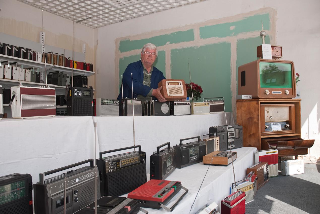 DEU, Deutschland, Brandenburg, Eisenhüttenstadt. Der ehemalige Traktorist und  Stahlwerker im Ruhestand Rainer Kroll, 67 Jahre, mit dem Radiomodel Libelle 4D61 von 1954. Er sammelt alte DDR Radios und Radiorecorder, repariert sie und plant ein Radiomuseum in Frankfurt/Oder einzurichten.
