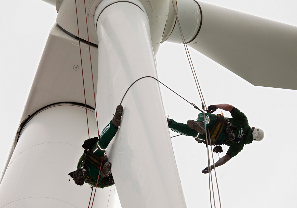 Industriekletterer pruefen routinemaessig  in luftiger Hoehe  die Aussenhaut der Rotorblaetter  einer Vestas Windenergieanlage mit Anlagennummer V 2163. Die beiden Klettermonteure der Seilpartner Windkraft GmbH, Rene Erhardt, 34 Jahre alt, weisser Helm, und Kevin Linge, 26 Jahre alt, orangener Helm, bei ihrer Arbeit in einem Windkraftpark. Abseilen vom Maschinenhaus einer Windkraftanlage entlang der Aussenhaut am Blatt, um Schaeden, auch mit digitaler Kleinbildkamera, zu dokumentieren, Gutachten zu erstellen oder kleinere Beschaedigungen direkt vor Ort und in der Luft zu reparieren. Kleinweissandt bei Koethen, Sachsen Anhalt. 7. Mai 2010