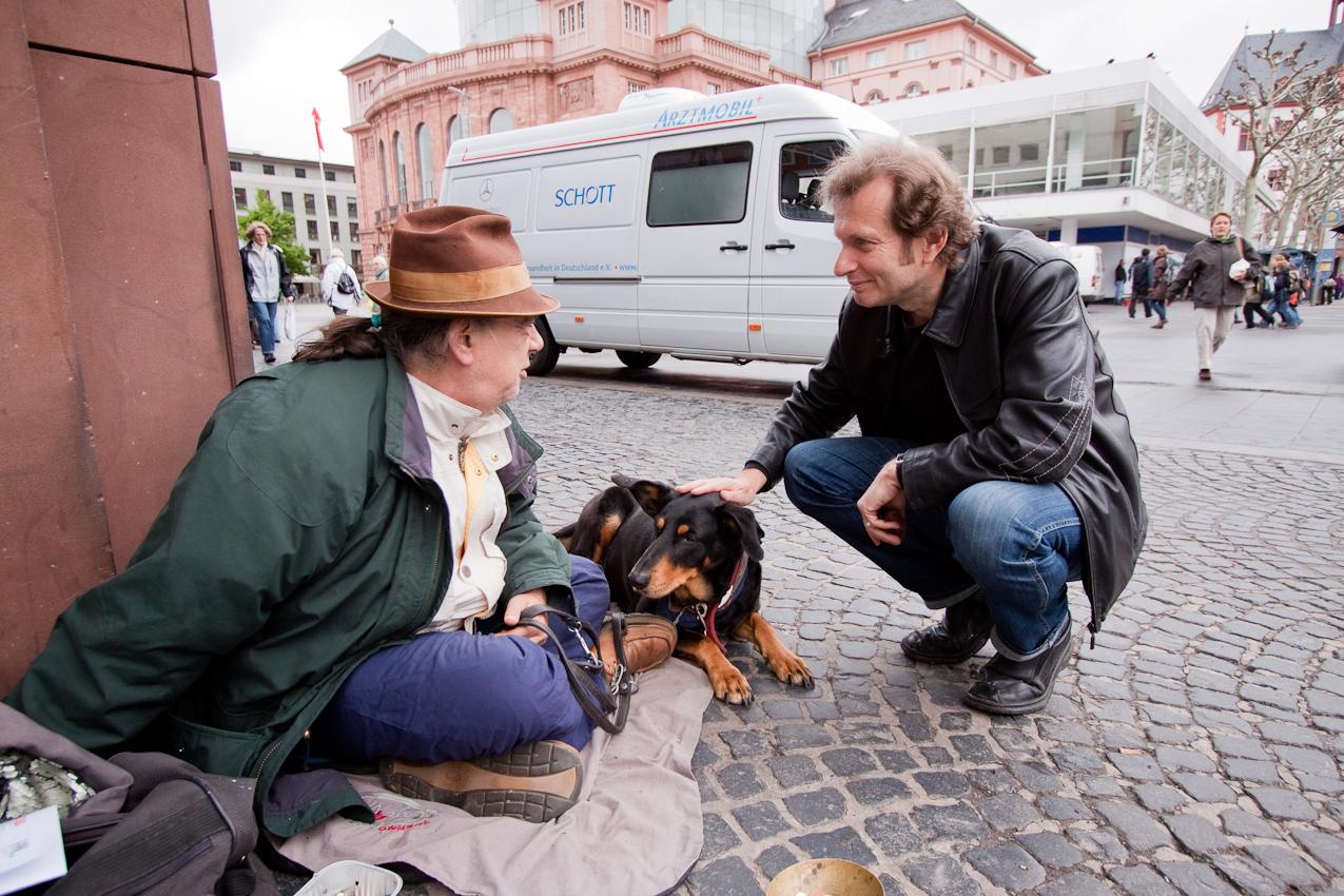Obdachlosen-Arzt Dr. Gerhard Trabert: Doktor Trabert spricht mit einem Obdachlosen in der Fussgängerzone in Mainz. Doktor Trabert ist neben seiner Professur fur Sozialmedizin ein Arzt fur Obdachlose in Mainz. In dieser Funktion fährt er auch mit seinem Arztmobil durch  Mainz und Bingen um Obdachlosen eine medizinische Grundversorgung zu bieten.