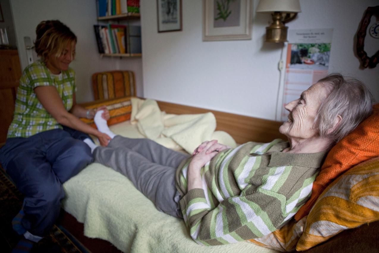 """Tägliche Massage: Enkeltochter Rita Lohmann massiert ihrer Oma die Füße, damit sie keine Wassereinlagerungen bekommt. Rita ist Ergotherapeutin und kennt sich mit der Pflege von alten Menschen aus: ,,Hauptsache ist, dass meine Oma nicht leiden muss und dass sie es so bequem wie möglich hat."""" Rita hat immer lustige Kommentare auf den Lippen und bringt ihre Oma ständig zum Lachen."""