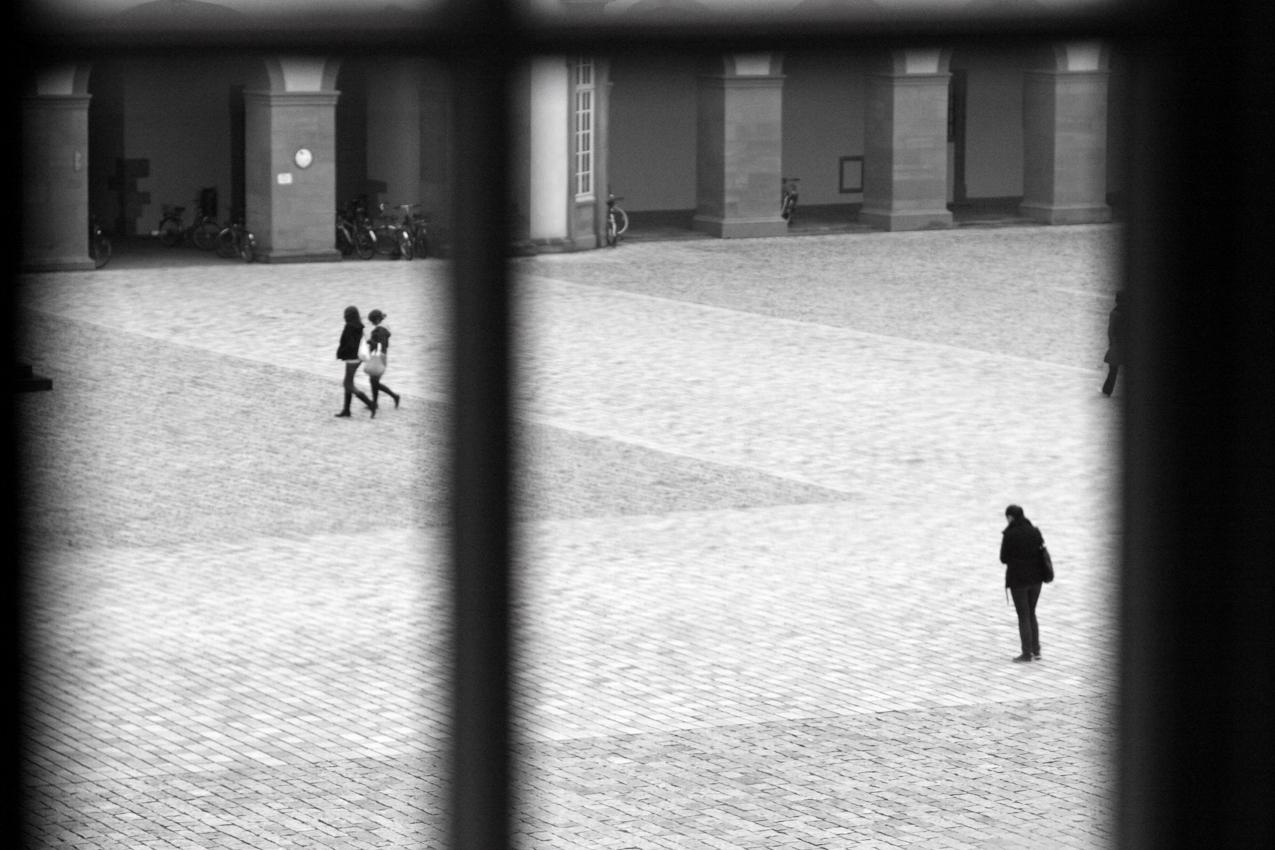 Studenten laufen im Hof der Universität Mannheim. Das Foto wurde durch ein Fenster eines Universitätsraums um 14:00 aufgenommen.