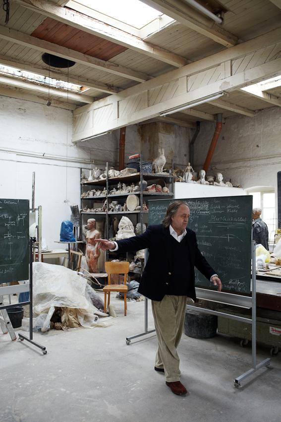 Der Bildhauer und Meisterschüler von Josef Beuys, Wolfgang Genoux am 7. Mai 2010 bei einer Begehung der Atelierräumen der Freien Kunstschule Hamburg - FIU / Free International University e.V. gemeinnützig ( gegründet 1980 ), welche er mitbegründete und in der er seit 30 Jahren lehrt. An den Tafeln finden sich diagrammartige Schaubilder zur Erläuterung  seiner Kunsttheorie.