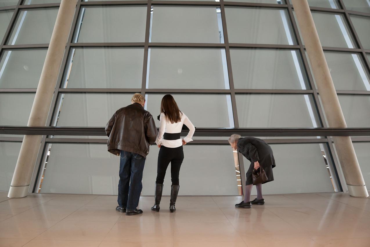 Reichstag, Fraktionsebene. Besucher - junges Pärchen und alte Frau - versuchen, durch die während der Debatten zugehängten Fenster einen Blick in den Plenarsaal zu erhaschen.