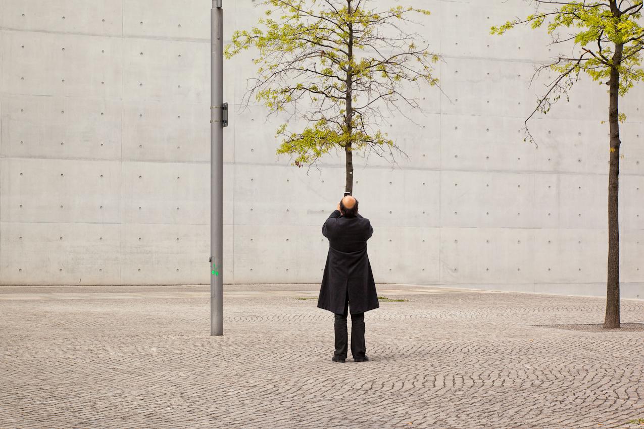 Paul-Loebe-Haus. Tourist fotografiert einen Baum vor der Südseite des Paul-Loebe-Hauses.