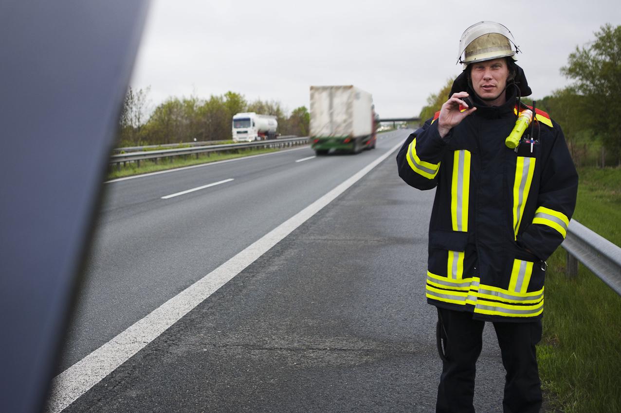 Fehlalarm - Feuerwehrmann Tim B. auf der BAB 27 vor einem vermeindlich brennenden Fahrzeug, das nur einen Kühlerschaden hatte.