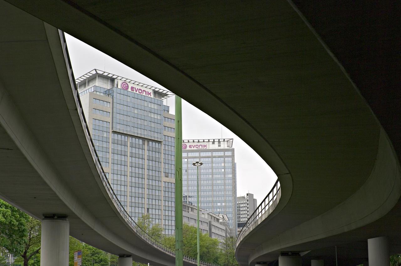 Der Gebäudekomplex Rellinghaus I und II von Evonik Industries AG gesehen durch die Trassen der Helbingbrücken der Stadtautobahn A40.