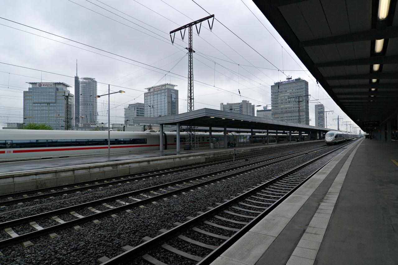 Blick über die Gleislandschaft des Essener Hauptbahnhofs mit durchfahrenden ICEs und der Skyline der südlichen Büro-City (v.l.nr.): Rellinghaus I der Evonik Industries AG (1996), Turm der RWE AG (1996), Rellinghaus II der Evonik Industries AG (1999) mit Nachbargebäude links, RWE-Gebäude/Huyssen-Allee (1980), RWE-Gebäude/Krupp-Straße (1961), Deutsche Postbank AG (1968), ThyssenKrupp AG (1960).