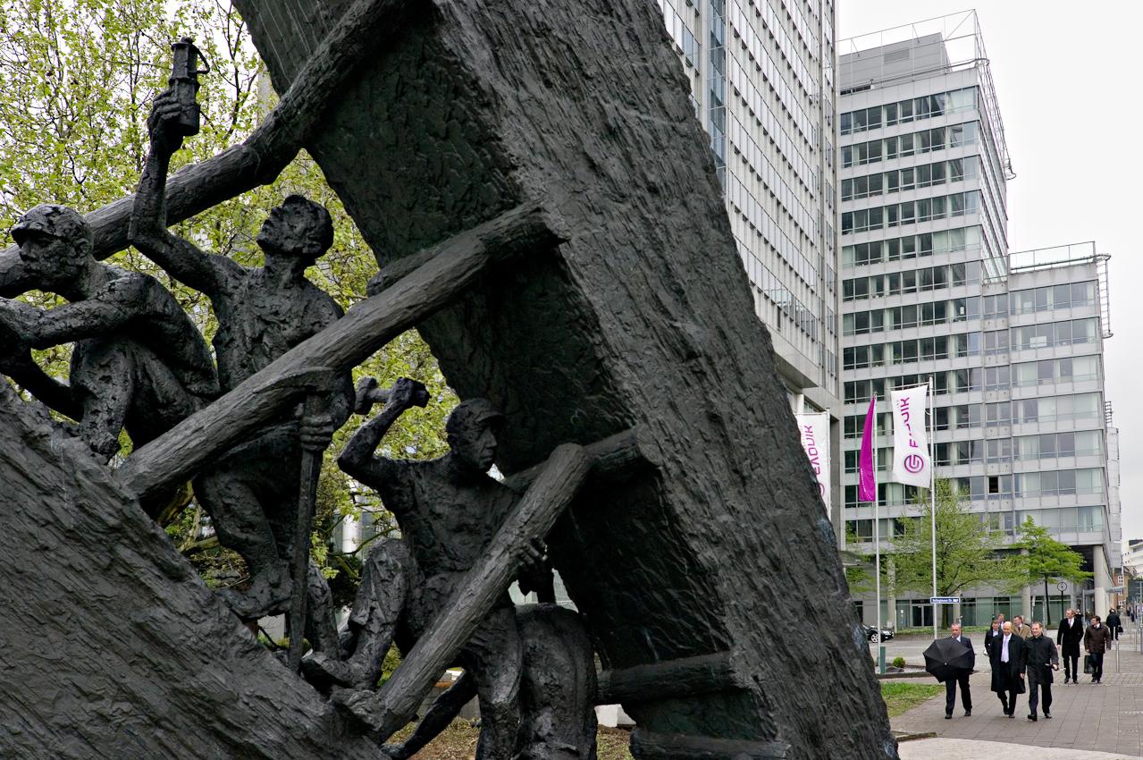 """Arbeitsszene (Detail) am Bergarbeiterdenkmal """"Steile Lagerung"""" von Bildhauer Max Kratz 1985 und Büro-Arbeiter auf dem Weg in die Pause vor der Kulisse des Rellinghaus von Evonik Industries AG."""