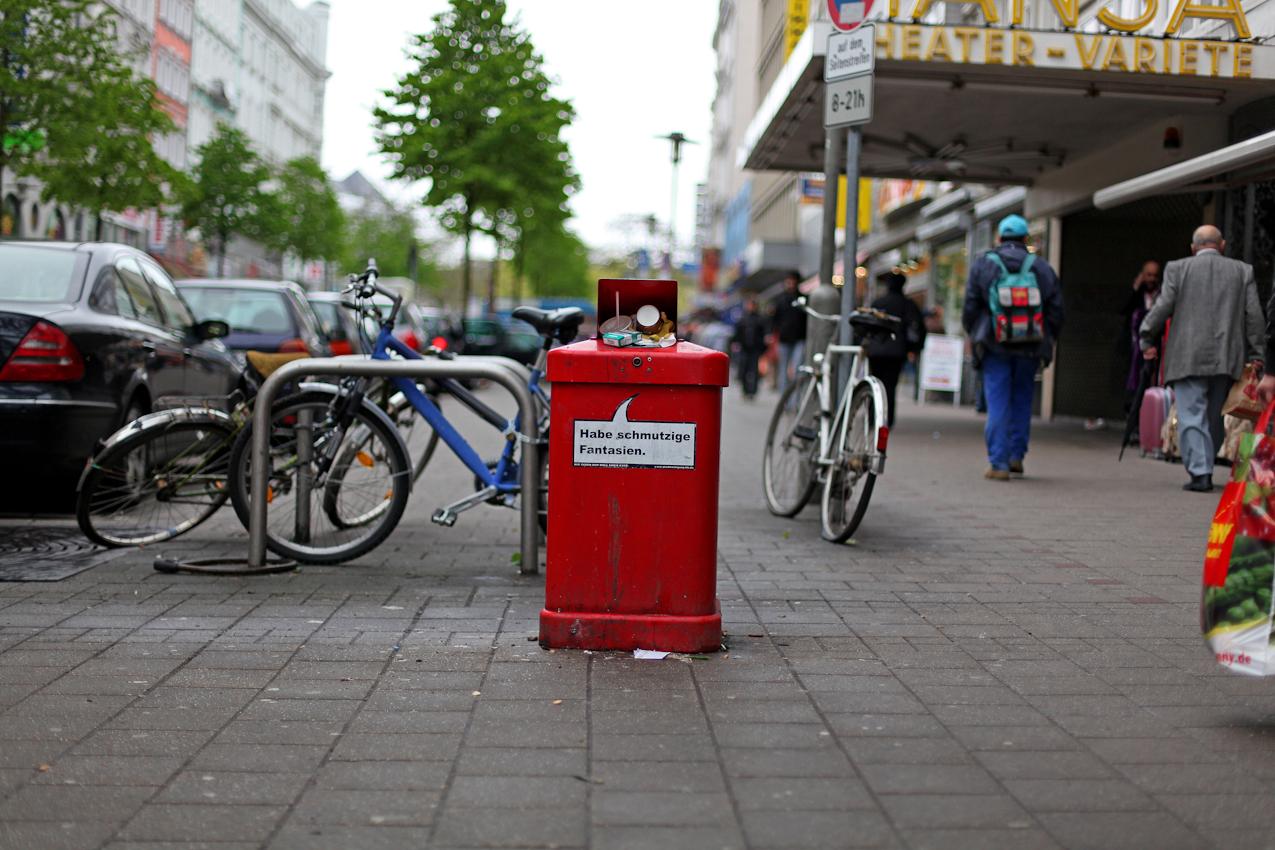 """Ein übervoller Mülleimer mit der Aufschrift """"Habe schmutzige Fantasien"""" am Hamburger Steindamm. Im Hintergrund ist das Hansa Variete Theater zu sehen sowie einige Passanten."""