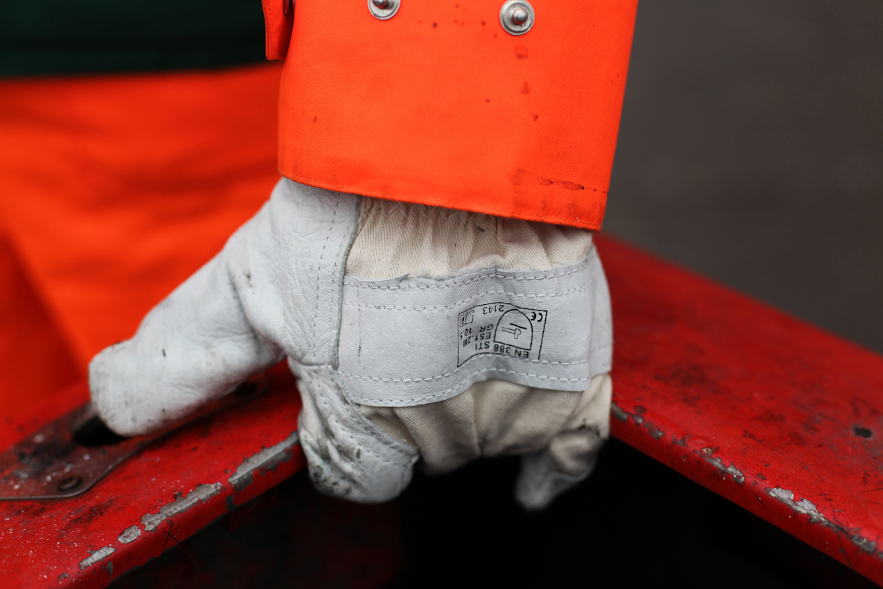 """Die Hand mit Arbeitshandschuh von Robert Szwejk, dem """"Hansaplatzkümmerer"""", an einem der roten Mülleimer am Hamburger Hansaplatz."""