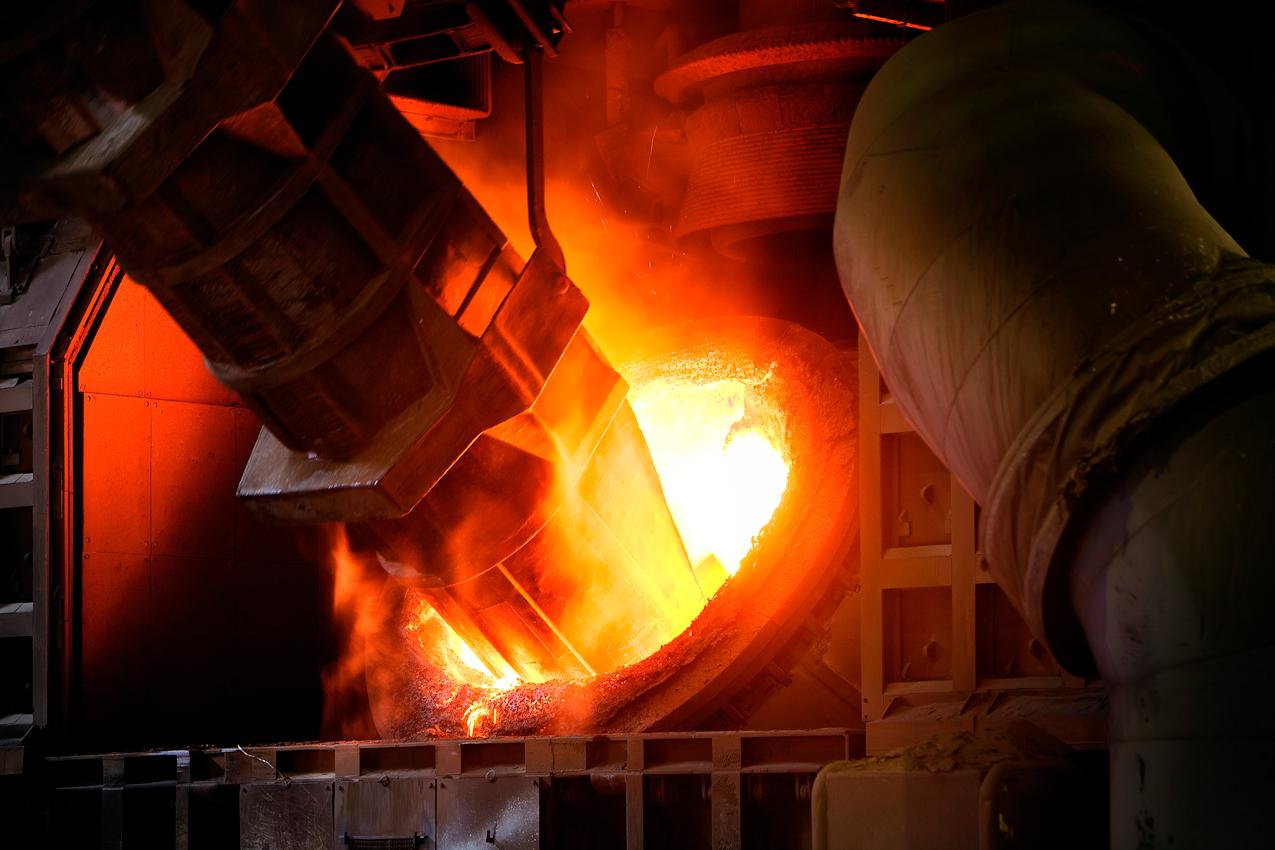 Konverter-Stahlwerk Beeckerwerth. Der Konverter wird chargiert: Die Schrottmulde (im Bild) befüllt den Konverter zweimal mit 30 to aufbereitetem Eisenschrott, anschließend wird mit der Roheisenpfanne 240 to Roheisen in den Konverter gekippt. Aus Schrott, Roheisen und der Hinzugabe von Sauerstoff unter hohem Druck entsteht flüssiger Rohstahl.