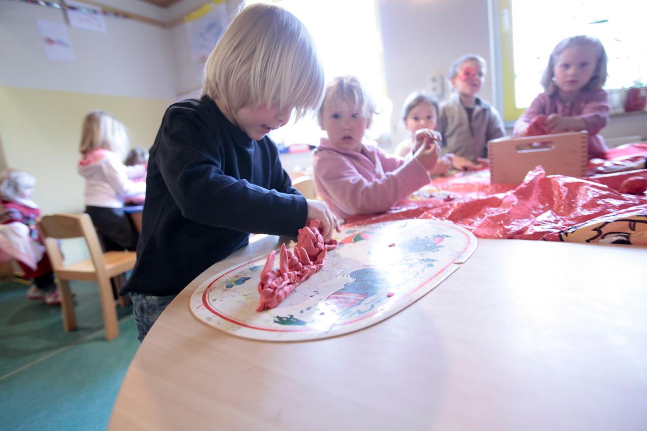 """Niclas (5) baut im Rahmen der ,,Spielzeugfreien Woche"""" im Kindergarten eine Eisenbahndampfmaschine aus Knetmasse."""
