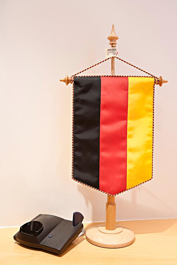 Schwarz-Rot-Gelb. Produktion eines Nationalsymbols. Tischbanner mit Preisschild (18,60 Euro) neben einer Telefon-Station hinter dem Empfangstresen.