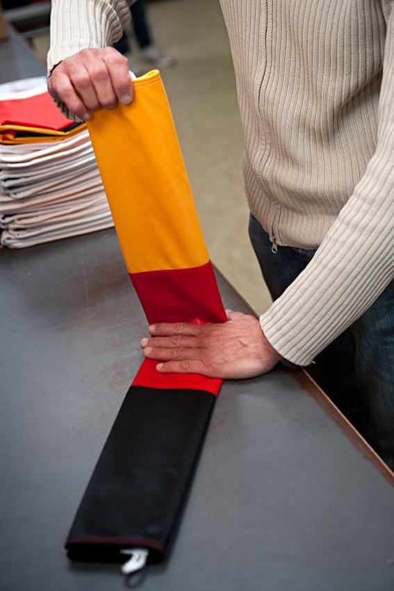 Der Lagermanager legt eine Deutschlandfahne zusammen, bevor sie eingeschweißt wird und ins Lager kommt.