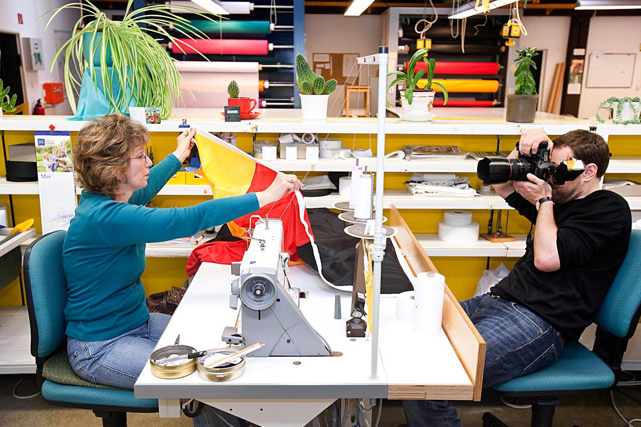 Thies Raetzke fotografiert die Herstellung von Deutschlandfahnen bei der Firma FahnenFleck in Pinneberg, hier die Naeherin Sabine Ostermann beim Saeumen einer Deutschlandfahne.
