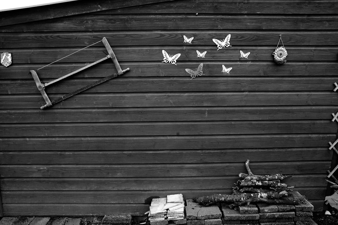 """Eine typische Wand eines Gartenhäuschens mit einer hängenden Säge und interessanterweise Plastikschmetterlingen, obwohl man ja in der """"Natur"""" ist, eine weitere Betonung auch durch die künstliche Blüte daneben. Zu sehen auch noch ein kleines Wappen, die Menschen zeigen gerne woher sie kommen, wohin sie sich zugehörig fühlen."""