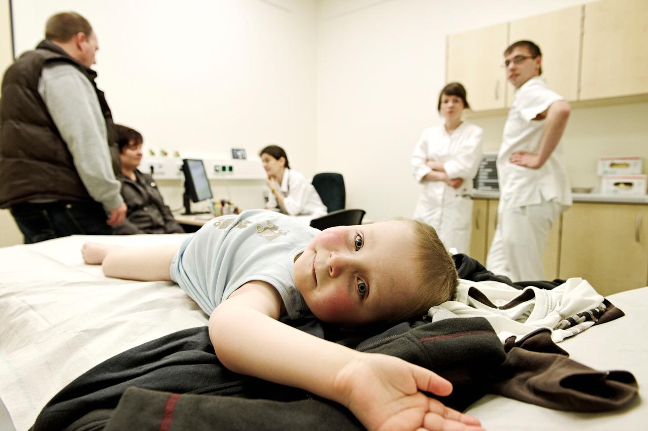 Jannis zusammen mit seinen Eltern, Ärzten und Pflegern während einer Kontrolluntersuchung nach seiner Chemotherapie im Untersuchungsraum der Ambulanz.