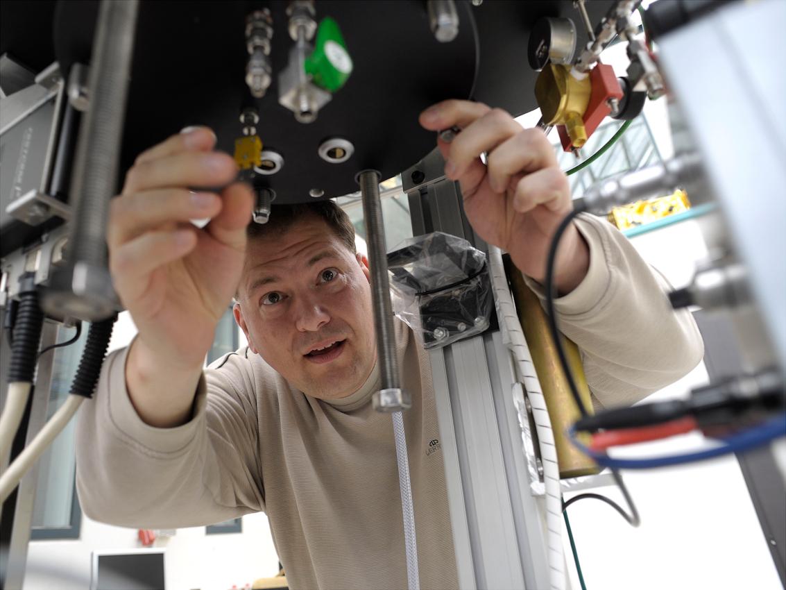 Dipl. Ing. Michael Peters (ZARM) verschließt die Druckkammer, in der das Experiment stattfindet. Die Kammer ist schon im Skelett der Fallkapsel montiert.