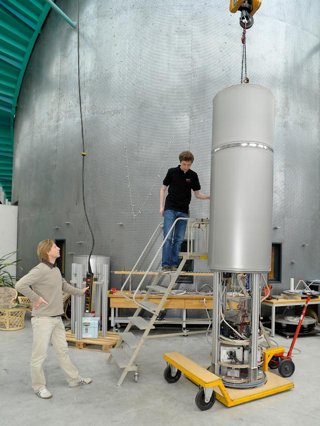 Dipl. Ing. Simon Mawn (l.) und Dipl. Ing. Michael Heseding (r., beide ZARM) montieren die Fallkapsel. Mit einem Kran wird die äußere Hülle über den Experimentaufbau gesenkt.