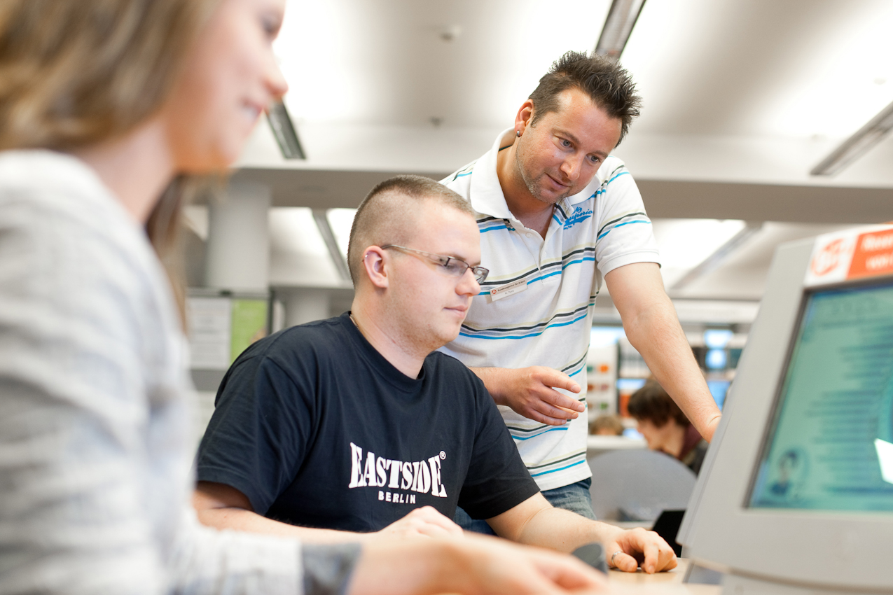 Knut Tyra erklärt einem Jugendlichen im BIZ die Möglichkeiten der Arbeitssuche und Information uber Ausbildungsberufe.