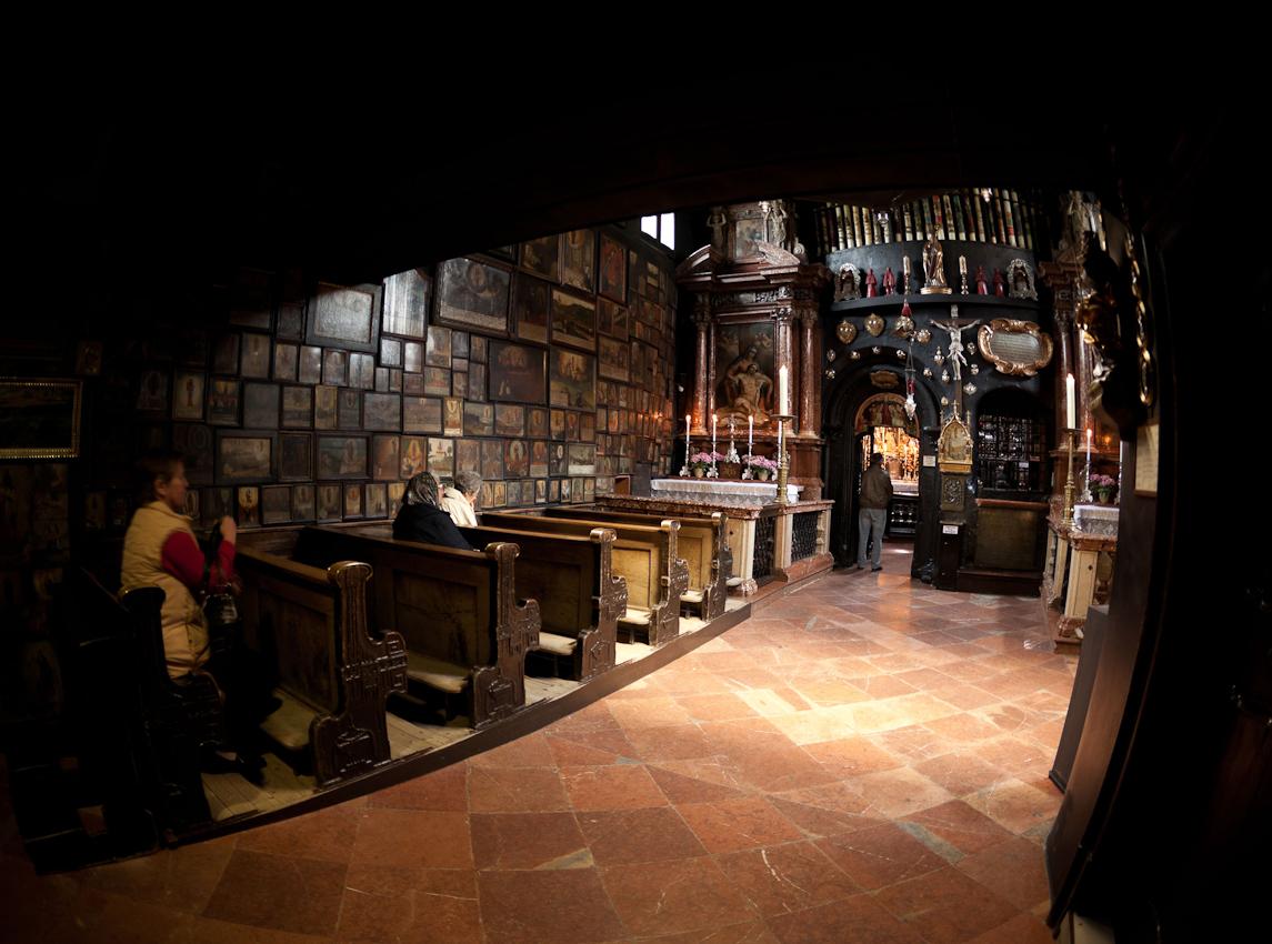 """Betende in der Gnadenkapelle in Altötting. Die Kapelle beherbergt seit dem 14. Jahrhundert die sogenannte """"schwarze Madonna"""", der im Jahre 1489 eine Wunderheilung zugeschrieben wurde und ist seit dem zu einem der zentralen Orte der Marienverehrung geworden. Unzählige Votivtafeln und -gaben zeugen von Fällen, in denen die Anbetung der Heiligen Mutter Gottes den Menschen in höchster Not geholfen hat. In der Kapelle befinden sich zahlreiche silberne Herzurnen, unter anderem mit den Herzen der verstorbenen Oberhäupter des Hauses Wittelsbach."""