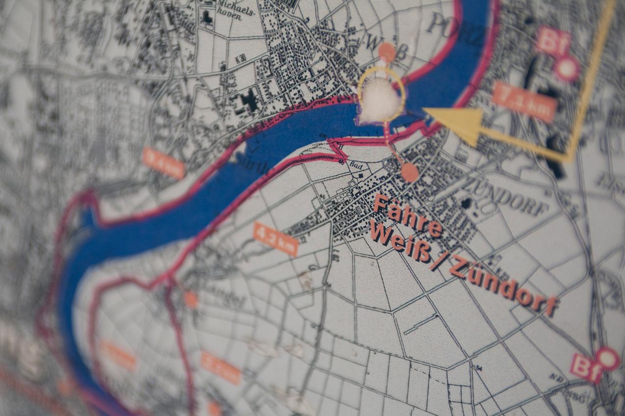 Hiweisschild am Weißer Rheinbogen mit einer Karte des Rheinverlaufs, auf der die Fähre von Weiß nach Zündorf eingezeichnet ist.