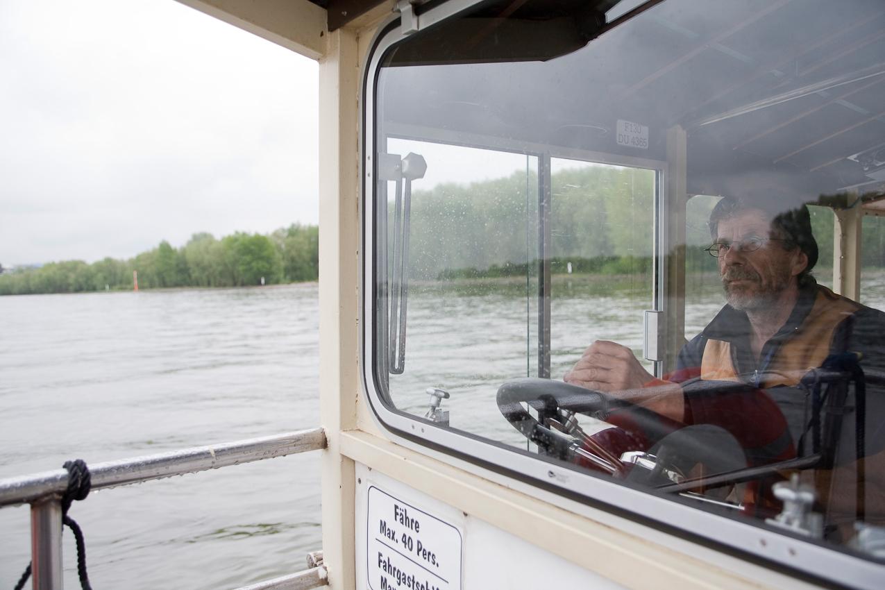 Der Fährmann Heiko Dietrich am Steuer des Krokolino auf dem Rhein zwischen Köln Weiß und Köln Zündorf.