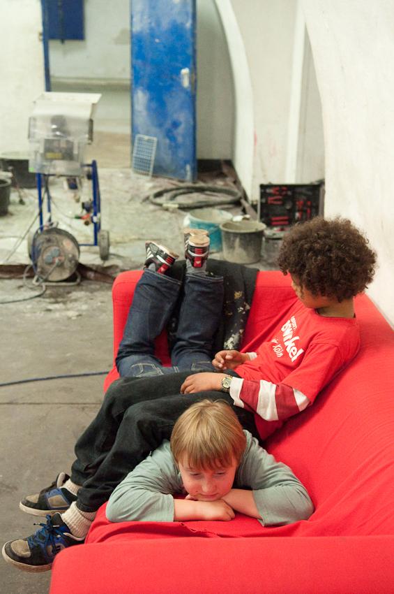 """Zwei Jungs ruhen sich auf einem Sofa im Jugendzentrum Bauspielplatz aus. Aufgenommen um 15:53 Uhr.  Der """"Baui"""" ist eine offene Kinder- und Jugendeinrichtung mit Übermittagbetreuung im alten Fort 1 im Friedenspark der Kölner Südstadt. Adresse: Hans-Abraham-Ochs-Weg 1. Aufgenommen um 15:53 Uhr. Der """"Baui"""" ist eine offene Kinder- und Jugendeinrichtung mit Übermittagsbetreuung im alten Fort 1 in der Kölner Südstadt. Ein vielseitiges Freizeitangebot sorgt hier neben dem Bauspielplatz fur sinnvolle Freizeitgestaltung. Mit im Programm sind Mädchen-, Jungen-, Koch-, und Computergruppen, ein Proberaum, Selbstverteidigungstrategien, eine Fahrradwerkstatt, 4 Fußballmannschaften für Jungen und Mädchen, Discos; Geisterkeller; Ferienfreizeiten; Musical-Produktion; Besonderheiten; altes Fort (""""Rheinschanze"""") im Park; umgeben von Wällen und Gräben; 2.500 m2 großes Außengelände mit unterirdischem Gang; Remisen; Schiff; Feuer- und Wasserstelle; Garten; Möglichkeit zum Hüttenbau; große Halle; z.B. für Tischtennis und Billard; bei schlechtem Wetter auch zum Inliner-Fahren oder für Feste; Judo- und Kraftsportraum; BesucherInnen; Kinder und Jugendliche von 6-20 Jahren und mehr."""