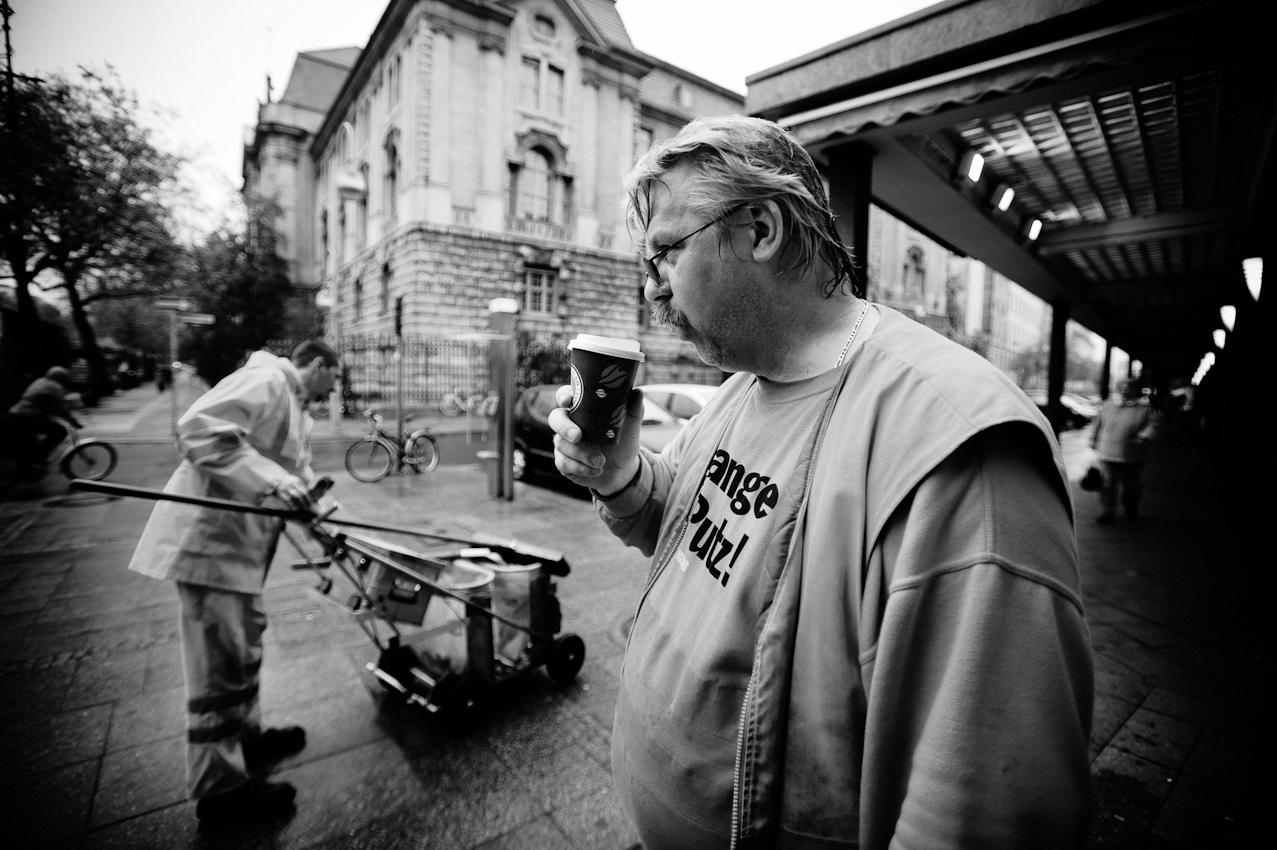Einen Becher Kaffee gönnt sich Stephan Wittzack (47), Mitarbeiter der Berliner Stadtreiningung (BSR) um kurz nach 07.00 Uhr am Bahnhof Zoo. Zusammen mit seinem Kollegen Uwe Pahl (42, im Hintergrund) ist er für die Reinigung von Straßen, Plätzen und Gehwegen rund um den Bahnhof Zoo und den Kurfürstendamm verantwortlich.