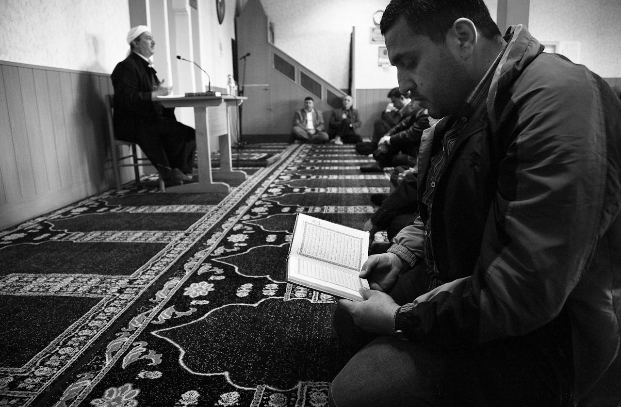 Der Mann im Vordergrund liest den Koran auf Arabisch, da er wahrscheinlich kein Türkisch kann und deswegen der Predigt (khutba) des Imams nicht folgen kann. Der Imam wechselt während der Predigt zwar zwischen Türkisch und Arabisch. Da er aber selber aus der Türkei kommmt, spricht er den Großteil der Predigt auf Türkisch. Nicht alle Gläubigen, die in der Takva-Moschee Leipzig zum Gebet erscheinen, sprechen Türkisch.
