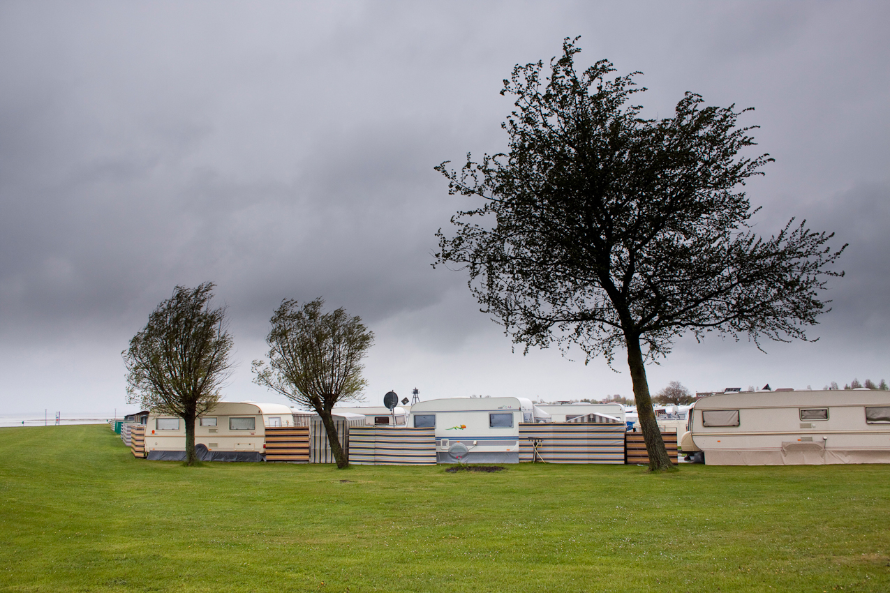 Schillig, einer der größten Campingplätze Deutschlands, gelegen an der Nordsee und der Jademündung. Zivilisation an der Grenze zum UNESCO-Weltnaturerbe Wattenmeer. An diesem Tag nur endlose Weite, die im Dunst vergeht. Und auch das noch: Dauerregen der waagerecht mit auflandigem Starkwind von der Nordsee kommend gegen den Deich schlägt. Menschenleer und einsame Weite. Nur einmal zeigen sich einige ganz harte Nordicwalker und ziehen vorüber. Verlassen die 100 Quadratmeter Glückseligkeit hinter den gleichförmigen immer wiederkehrenden Windfängen. Verlassen auch die Strandkörbe. Dieser Tag an diesem Ort vergeht in Einsamkeit.
