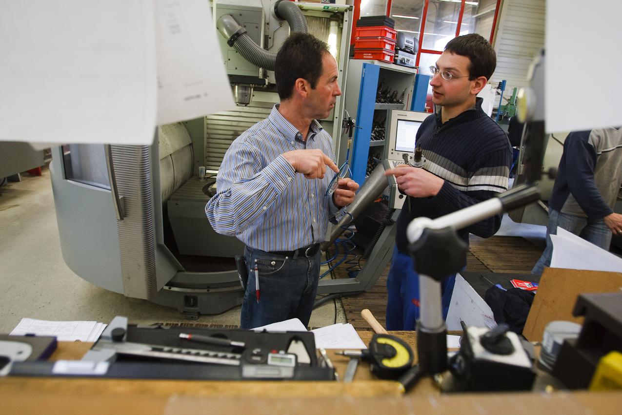 Der Geschäftsführer der Firma Color Metal, Otmar Gutmann, steht mit seinem Mitarbeiter Steffen Schniepper in der Werkshalle der Firma und bespricht mit ihm den Einsatz einer Erodiermaschine. Heitersheim im Markgräflerland am 7. Mai 2010 um 10:05.