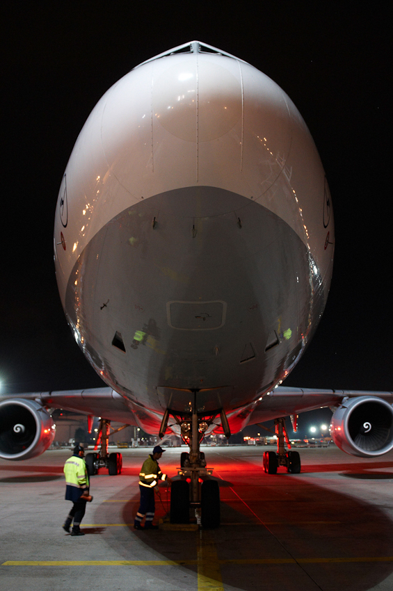 Fraport Mitarbeiter nehmen den Lufthansa Freighter MD-11 in der Parkposition am Entladestandort in Empfang.