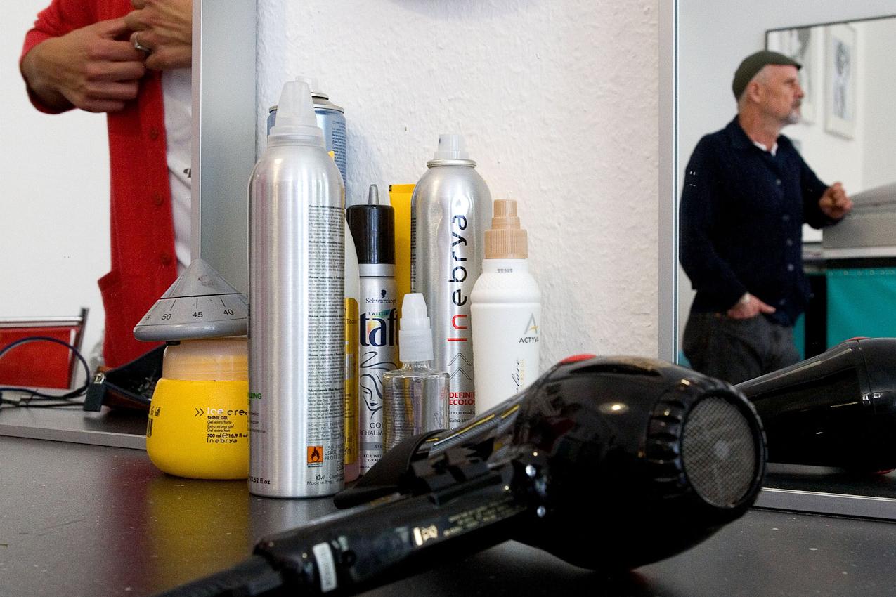 Im Geschäft des Friseurs Ciro Boschetto: Das Bild zeigt Sprayflaschen und Haarfön; im Spiegel rechts sieht man Ciro Boschetto, links seinen Assistenten Andrea Acciarino.