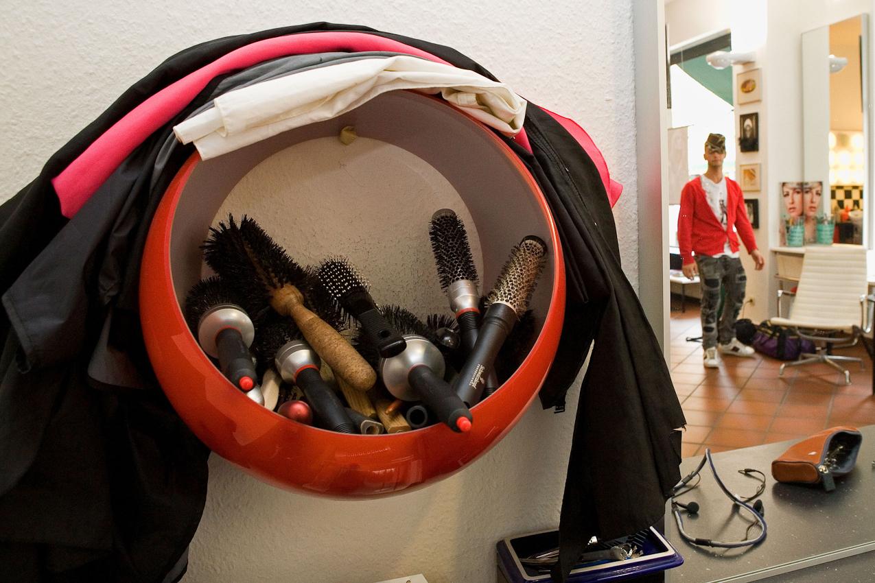 Haarbürsten in einem Korb; im Spiegel sieht man Andrea Acciarino, Cro Boschettos Assistenten.