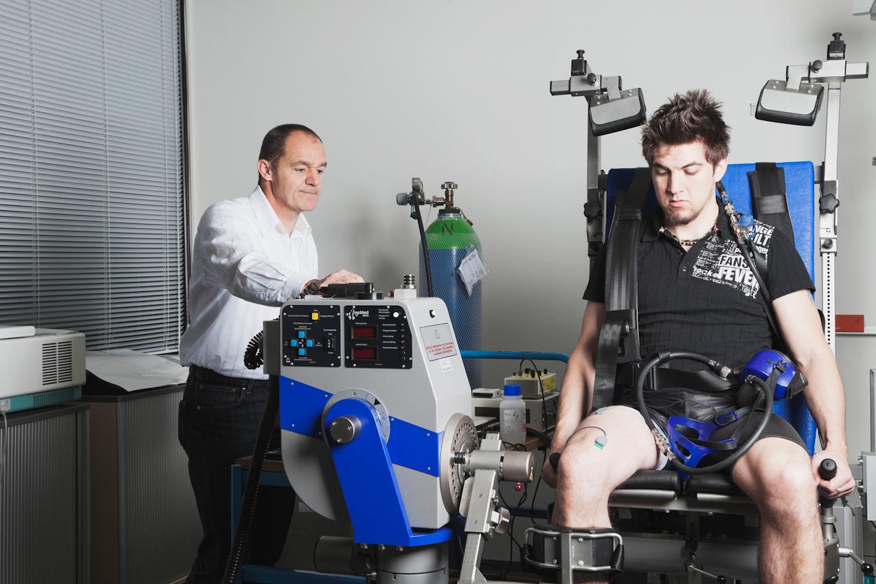 Der Proband Fabian Schurg (rechts) sitzt auf einer elektronisch gesteuerten Kraftmaschine. Auf dem rechten Oberschenkel sind die Elektroden für die Muskelaktivitätsmessung angebracht. Dr. Axel Knicker (links) überprüft die Signalqualität bei Muskelanspannung.