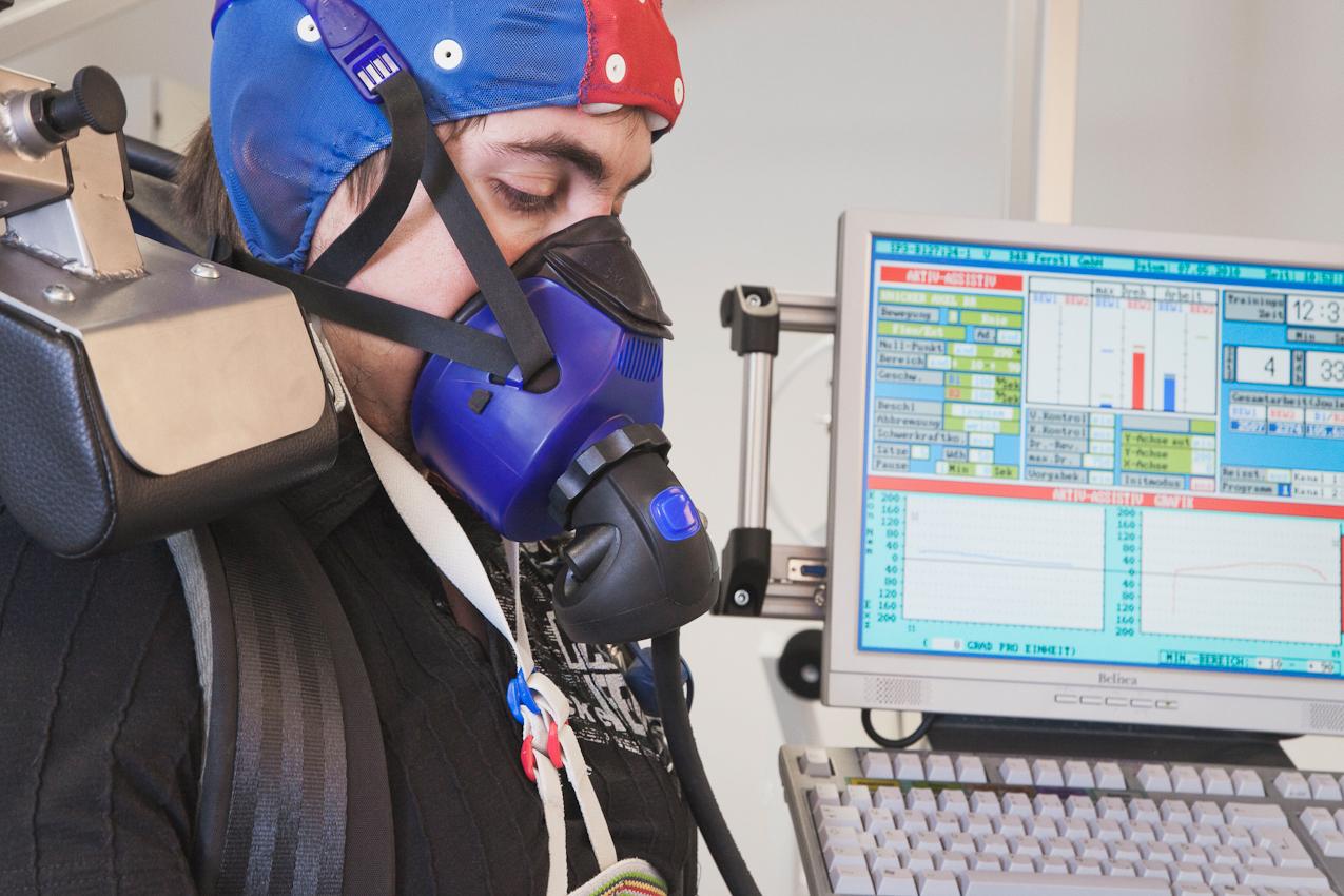 Über die Atemmaske atmet Proband Fabian Schurg sauerstoffarme Luft, während die Beinelektroden die Muskelaktivität messen und die EEG-Kappe die Hirnströme aufzeichnet. Im Hintergrund informiert ein Computermonitor über die aktuellen Kraftwerte.