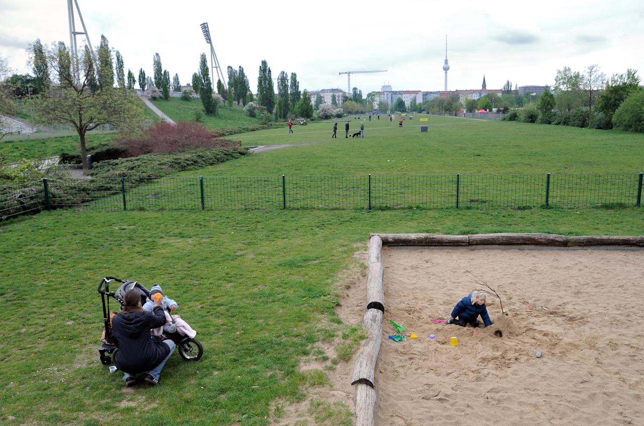 Mutter mit Baby und ein im Sand spielendes Kind, links die Flutlichtmasten des Cantian-Stadions.